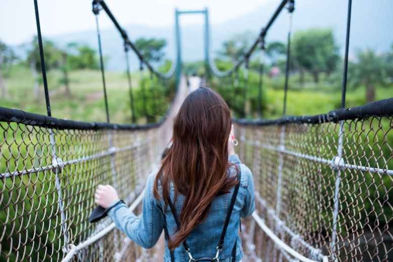 woman in blue long sleeved dress on rope bridge